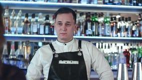 Εύθυμος νέος μπάρμαν που χαμογελά και που μιλά στον πελάτη στο φραγμό απόθεμα βίντεο