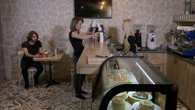 Εύθυμος νέος ξανθός εξυπηρετώντας καφές εργαζομένων barista για να πάει σε έναν θηλυκό πελάτη σε έναν καφέ - απόθεμα βίντεο