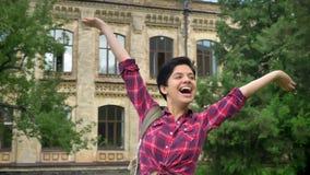 Εύθυμος νέος φοιτητής πανεπιστημίου με τη σύντομη μαύρη τρίχα ενθαρρυντική και το χαμόγελο, που στέκεται στο πάρκο κοντά στο πανε απόθεμα βίντεο