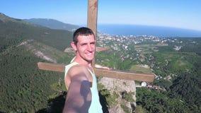 Εύθυμος νεαρός άνδρας που αυξάνει τα χέρια του υψηλά πάνω από το μεγάλο δύσκολο βουνό με το σταυρό απόθεμα βίντεο
