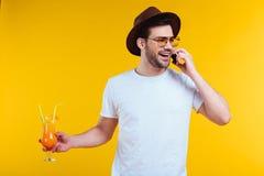 εύθυμος νεαρός άνδρας στο καπέλο και γυαλιά ηλίου που κρατούν το ποτήρι του θερινού κοκτέιλ και που μιλούν από το smartphone Στοκ Εικόνες
