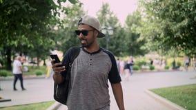 Εύθυμος νεαρός άνδρας στο καπέλο του μπέιζμπολ που περπατά στην οδό και τον καφέ κατανάλωσης απόθεμα βίντεο