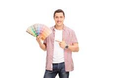Εύθυμος νεαρός άνδρας που κρατά swatch χρώματος Στοκ Εικόνες