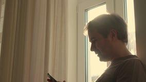 Εύθυμος νεαρός άνδρας που χρησιμοποιεί το έξυπνο τηλέφωνό του από το παράθυρο 4K πυροβολισμός σχεδιαγράμματος απόθεμα βίντεο
