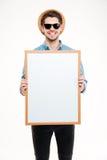 Εύθυμος νεαρός άνδρας στο καπέλο και γυαλιά ηλίου που κρατούν κενά whiteboard Στοκ φωτογραφία με δικαίωμα ελεύθερης χρήσης