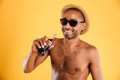 Εύθυμος νεαρός άνδρας στο καπέλο και γυαλιά ηλίου που πίνουν το κοκ Στοκ φωτογραφίες με δικαίωμα ελεύθερης χρήσης