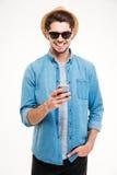 Εύθυμος νεαρός άνδρας στο καπέλο και γυαλιά ηλίου που χρησιμοποιούν το smartphone Στοκ φωτογραφία με δικαίωμα ελεύθερης χρήσης