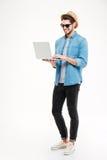 Εύθυμος νεαρός άνδρας στο καπέλο και γυαλιά ηλίου που χρησιμοποιούν το lap-top Στοκ φωτογραφία με δικαίωμα ελεύθερης χρήσης