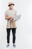 Εύθυμος νεαρός άνδρας στο καπέλο που στέκεται και που χρησιμοποιεί το lap-top Στοκ Εικόνες