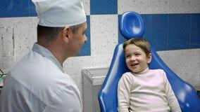 Εύθυμος οδοντίατρος ατόμων που μιλά στο μικρό παιδί φιλμ μικρού μήκους