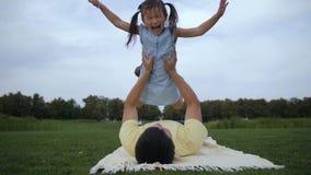 Εύθυμος πατέρας που ανυψώνει επάνω τη χαριτωμένη κόρη υπαίθρια φιλμ μικρού μήκους
