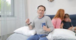 Εύθυμος πατέρας που χρησιμοποιεί τα νέα ακουστικά που ακούνε τη μουσική στην κρεβατοκάμαρα πέρα από τη μητέρα που επικοινωνεί με  φιλμ μικρού μήκους