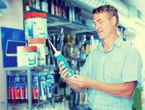 Εύθυμος πελάτης ατόμων που επιλέγει το σωλήνα στεγανωτικής ουσίας στην υπεραγορά Στοκ φωτογραφία με δικαίωμα ελεύθερης χρήσης