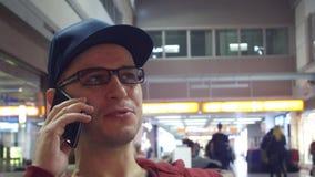 Εύθυμος προγραμματιστής στα μαύρα γυαλιά πλαισίων που μιλούν στο κινητό τηλέφωνό του στον αερολιμένα 4K βίντεο απόθεμα βίντεο