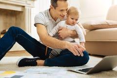 Εύθυμος προσεκτικός πατέρας που δείχνει την οθόνη παρουσιάζοντας κινούμενα σχέδια Στοκ Εικόνες