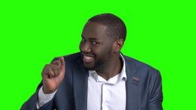 Εύθυμος σκοτεινός-ξεφλουδισμένος επιχειρηματίας στην πράσινη οθόνη απόθεμα βίντεο