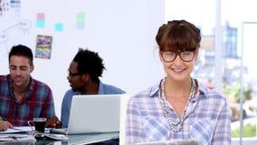Εύθυμος σχεδιαστής που θέτει ενώ οι συνάδελφοί της εργάζονται από κοινού απόθεμα βίντεο