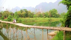 Εύθυμος τουρίστας που διασχίζει τη γέφυρα μπαμπού με τη μοτοσικλέτα, άποψη ασβεστόλιθων, Λάος απόθεμα βίντεο