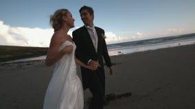 Εύθυμος το ζεύγος που περπατά και που φιλά στην παραλία απόθεμα βίντεο