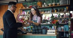 _εύθυμος τύπος αγοράζω δέσμη λουλούδι πληρώνω με smartphone μιλώ χαμογελώ