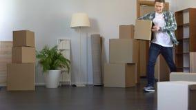 Εύθυμος τύπος που έρχεται με το κιβώτιο εγγράφου στο νέο νοικιασμένο διαμέρισμά του, ακίνητη περιουσία απόθεμα βίντεο