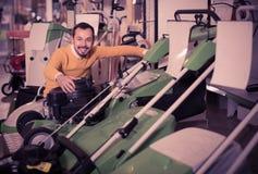 Εύθυμος τύπος που αποφασίζει σχετικά με τον καλύτερο χορτοκόπτη στο κατάστημα εξοπλισμού κήπων Στοκ φωτογραφία με δικαίωμα ελεύθερης χρήσης