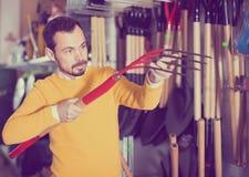 Εύθυμος τύπος που αποφασίζει σχετικά με το καλύτερο hayfork στο κατάστημα εξοπλισμού κήπων Στοκ Εικόνες