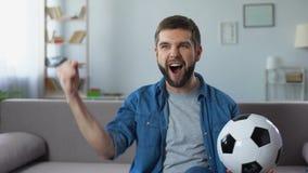 Εύθυμος τύπος που κραυγάζει δυνατά τον αγώνα ποδοσφαίρου προσοχής, επιτυχές αποτέλεσμα παιχνιδιών φιλμ μικρού μήκους