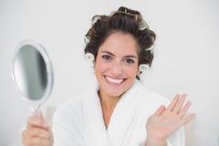 Εύθυμος φυσικός καθρέφτης και κυματισμός εκμετάλλευσης brunette Στοκ φωτογραφία με δικαίωμα ελεύθερης χρήσης