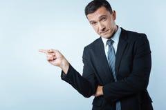Εύθυμος όμορφος επιχειρηματίας που δείχνει το αριστερό Στοκ φωτογραφία με δικαίωμα ελεύθερης χρήσης
