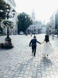 Εύθυμος όμορφος το ζεύγος κρατά τα χέρια τρέχοντας κατά μήκος της ηλιόλουστης πόλης οδού Κάθετη πίσω άποψη Στοκ Φωτογραφίες