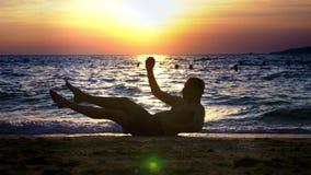 Εύθυμος όμορφος τύπος στα σορτς που κάνουν την ικανότητα, στην ακτή ενάντια στο σκηνικό ενός θαυμάσιου ηλιοβασιλέματος απόθεμα βίντεο
