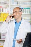 Εύθυμος ώριμος φαρμακοποιός στο τηλέφωνο στοκ εικόνα με δικαίωμα ελεύθερης χρήσης