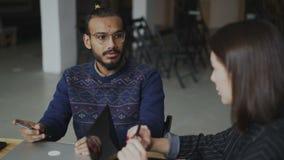 Εύθυμο άτομο αφροαμερικάνων στα γυαλιά που χαμογελούν και που συζητούν για το νέο πρόγραμμα ξεκινήματος με τη γυναίκα συνάδελφος  απόθεμα βίντεο