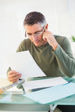 Εύθυμο άτομο με τα γυαλιά που διαβάζει το έγγραφο Στοκ Εικόνες