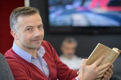Εύθυμο άτομο πλάγιας όψης στη βιβλιοθήκη Στοκ Φωτογραφία