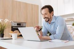 Εύθυμο άτομο που γελά εξετάζοντας το lap-top Στοκ εικόνα με δικαίωμα ελεύθερης χρήσης
