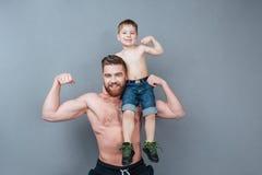 Εύθυμο άτομο που κρατά λίγο γιο στον ώμο και που παρουσιάζει δικέφαλους μυς Στοκ Φωτογραφία