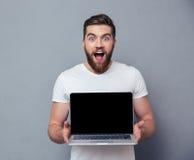 Εύθυμο άτομο που παρουσιάζει κενή οθόνη φορητών προσωπικών υπολογιστών στοκ εικόνα