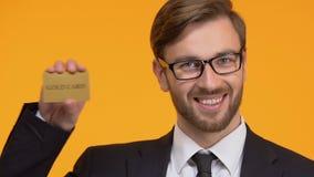 Εύθυμο άτομο που παρουσιάζει χρυσή κάρτα, ιδιότητα μέλους VIP λεσχών, προνόμια τραπεζών, κινηματογράφηση σε πρώτο πλάνο φιλμ μικρού μήκους