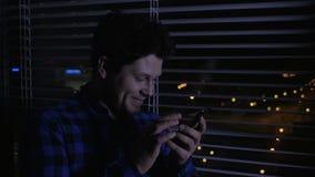 Εύθυμο άτομο που χρησιμοποιεί το smartphone τη νύχτα απόθεμα βίντεο