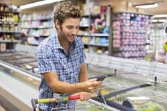 Εύθυμο άτομο που χρησιμοποιεί app το κινητό τηλέφωνο στο κατάστημα Στοκ Εικόνες