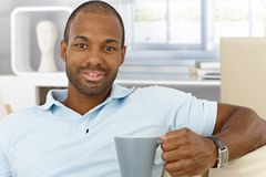 Εύθυμο άτομο στο σπίτι που έχει το τσάι στοκ φωτογραφίες