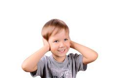Εύθυμο αγόρι 5 έτη που κλείνουν από τα αυτιά χεριών Στοκ Φωτογραφίες