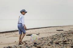 Εύθυμο αγόρι για να παίξει τη σφαίρα στην άμμο της θάλασσας στοκ φωτογραφία με δικαίωμα ελεύθερης χρήσης