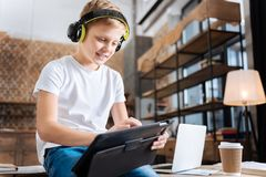 Εύθυμο αγόρι που δημιουργεί το playlist μουσικής στην ταμπλέτα Στοκ Εικόνα