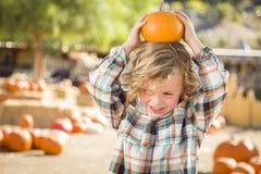 Εύθυμο αγόρι που κρατά την κολοκύθα του σε ένα μπάλωμα κολοκύθας Στοκ Φωτογραφία