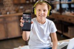 Εύθυμο αγόρι που παρουσιάζει τηλέφωνο με τη μουσική που ρέει app Στοκ Φωτογραφίες
