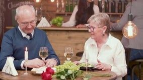 Εύθυμο ανώτερο ζεύγος κατά μια ρομαντική ημερομηνία σε ένα εστιατόριο απόθεμα βίντεο