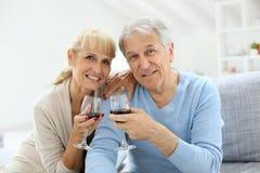Εύθυμο ανώτερο ζεύγος με ένα γυαλί του εορτασμού κρασιού Στοκ φωτογραφίες με δικαίωμα ελεύθερης χρήσης